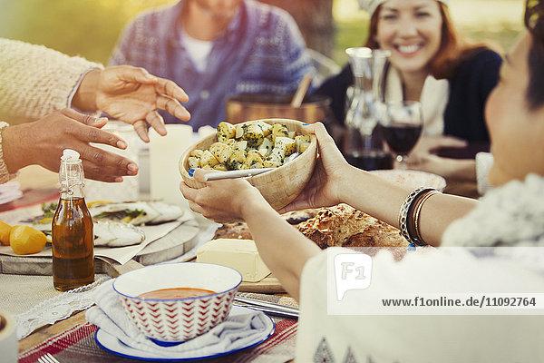 Freunde  die Essen über den Mittagstisch auf der Terrasse verteilen