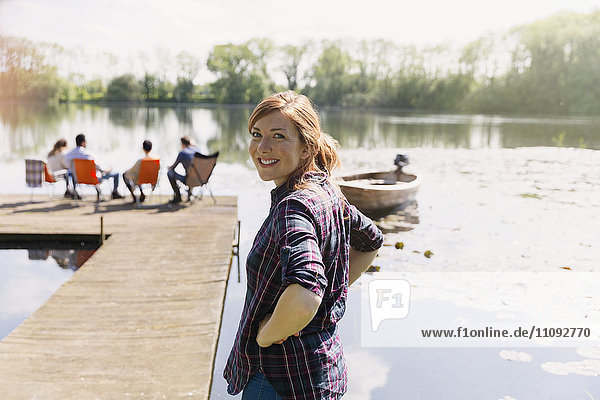 Porträt einer lächelnden Frau am sonnigen Ufer des Sees