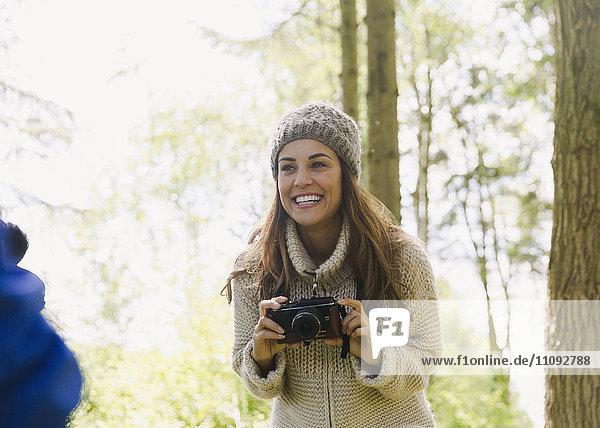 Lächelnde Frau mit Kamera im Wald