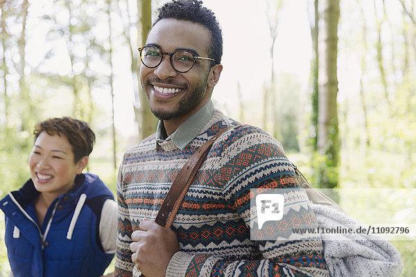Portrait lächelnder Mann mit Rucksackwanderung im Wald
