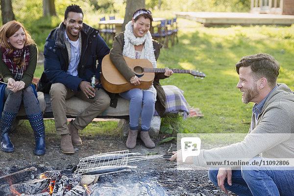 Freunde spielen Gitarre und kochen Fisch im Grillkorb am Lagerfeuer