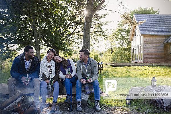 Freunde beim Biertrinken am Lagerfeuer vor der Hütte