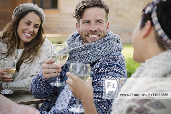 Lächelnde Freunde trinken Wein auf der Terrasse