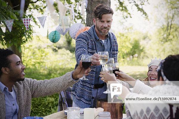 Freunde toasten Weingläser am Gartenparty-Tisch