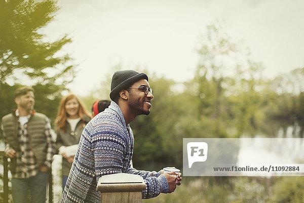Lächelnder Mann trinkt Kaffee auf dem Seebalkon