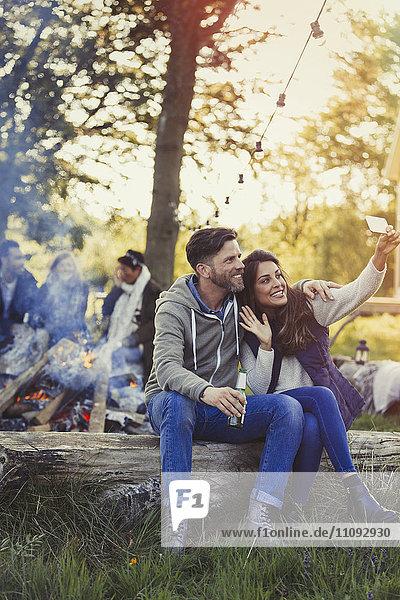 Paar posiert für Selfie mit Fotohandy am Lagerfeuer