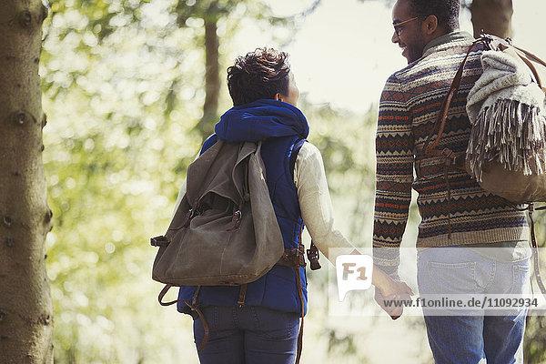 Paar mit Rucksäcken zum Händewandern im Wald