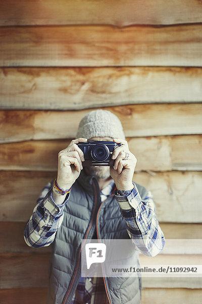 Portrait Mann mit Kamera außerhalb der Kabine