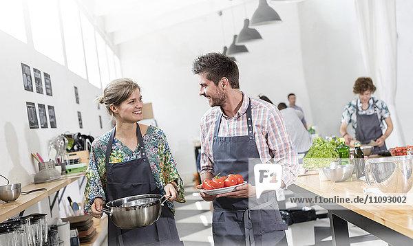 Paar mit Essen in der Küche des Kochkurses