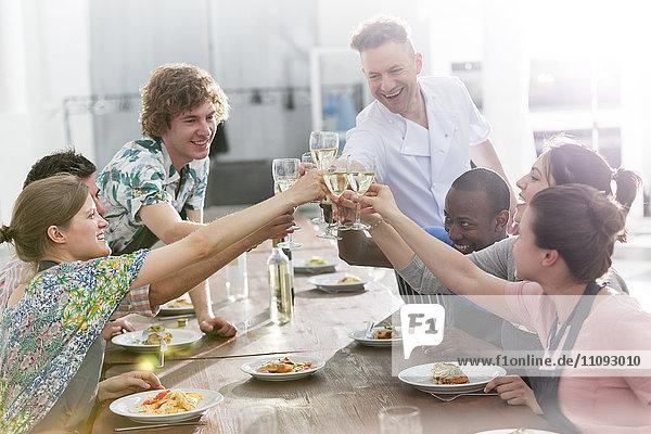 Kochlehrer und Schüler toasten Weingläser in der Küche des Kochkurses