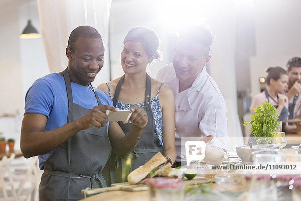 Mann fotografiert Essen in der Küche des Kochkurses