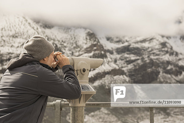 Mature man looking at view with telescope  Grossglockner mountain with Glacier Pasterze  National Park Hohe Tauern  Carinthia  Austria