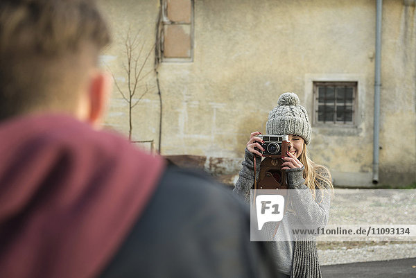 Teenage girl taking picture of her boyfriend with retro styled camera