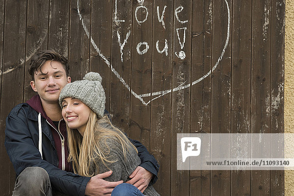Young couple hugging with a drawn heart and love you written on a wooden wall