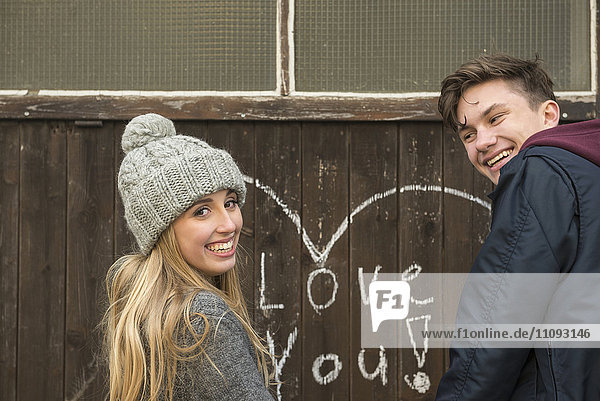Young couple standing near wall on which heart is drawn and love you written on a wooden wall
