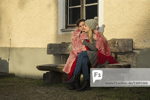 Young couple wrapped in a blanket and sitting on bench during sunset