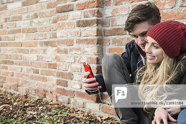 Young couple listening to music on mobile phone against brick wall