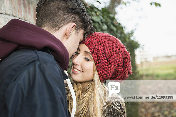 Young couple whispering something against brick wall