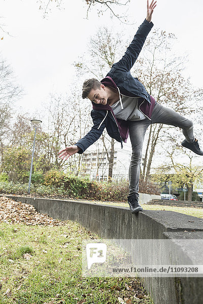 Young man balancing on concrete wall and loosing the balance Young man balancing on concrete wall and loosing the balance
