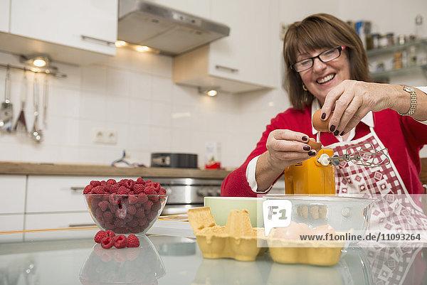 Senior woman dividing egg white and egg yolk in kitchen Senior woman dividing egg white and egg yolk in kitchen
