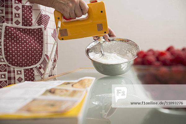 Senior woman mixing meringue in mixing bowl in kitchen