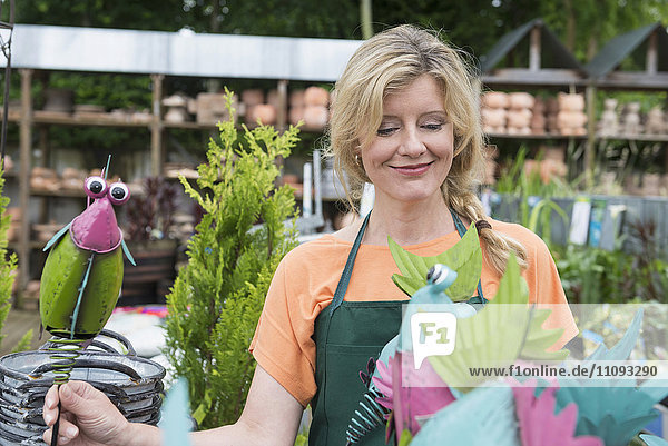 Female shop assistant showing fake birds in greenhouse  Augsburg  Bavaria  Germany