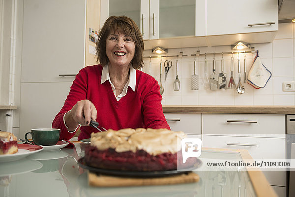 Senior woman cutting a meringue cake on dining table in kitchen