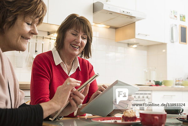 Two senior women using smart phone and digital tablet in kitchen