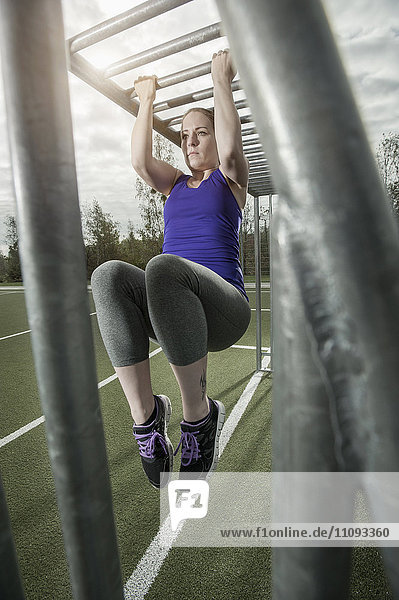 Young woman doing chin-ups on football ground