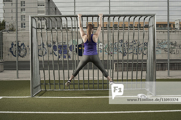 Rear view of a young woman doing chin-ups on football ground