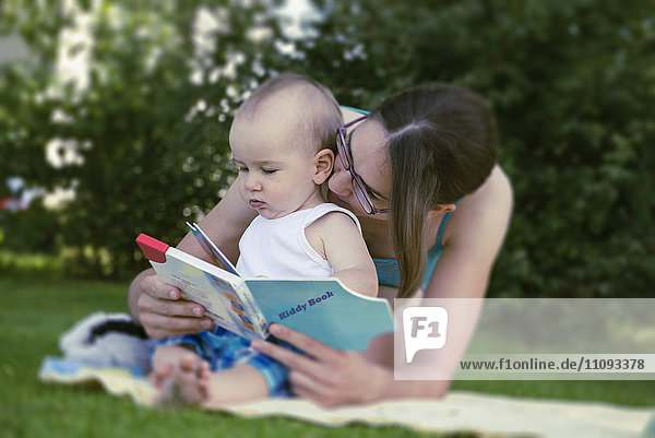 Mother and baby boy watching a picture book in lawn  Munich  Bavaria  Germany