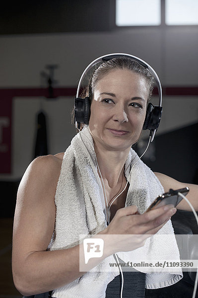 Young woman listening to music in the gym during the break