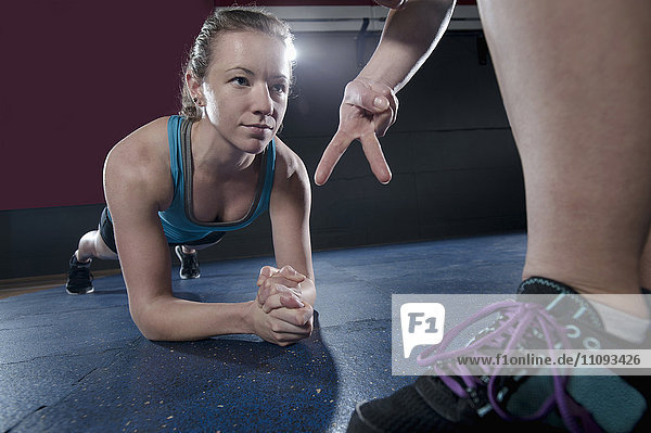 Fitness instructor giving training to client in the gym Fitness instructor giving training to client in the gym