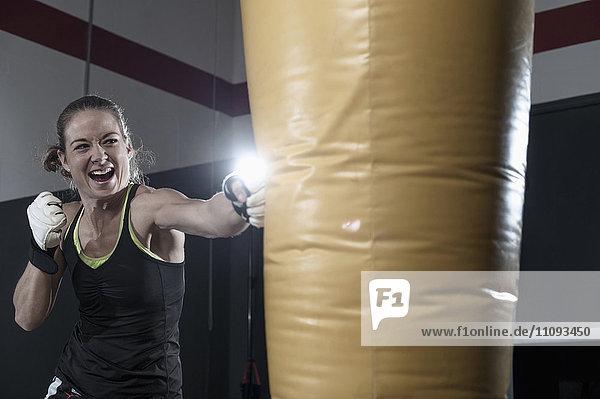 Sportswoman doing strength training by punching on punch bag in the gym Sportswoman doing strength training by punching on punch bag in the gym