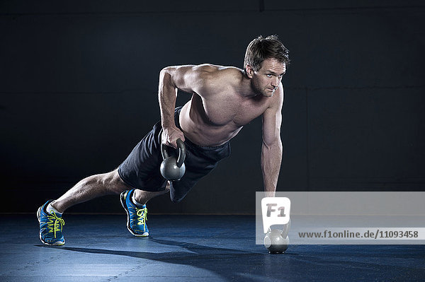 Athlete doing workout in fitness studio with Kettlebell