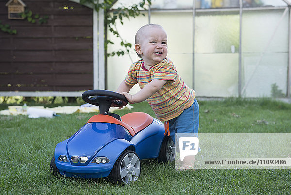 Baby boy with his toy car and crying in lawn  Munich  Bavaria  Germany Baby boy with his toy car and crying in lawn, Munich, Bavaria, Germany