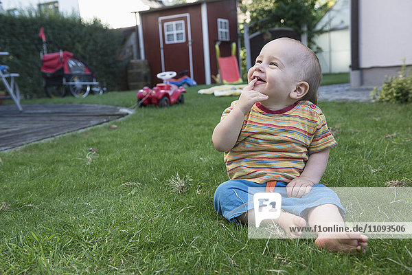 Little cute baby boy sitting on grass and laughing in a lawn  Munich  Bavaria  Germany
