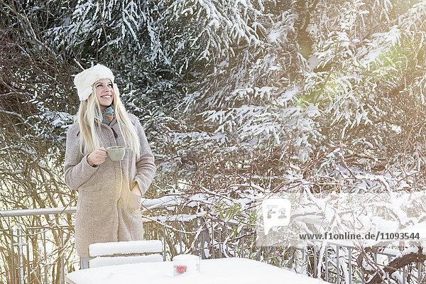 Teenage girl drinking coffee in winter season and looking up  Bavaria  Germany