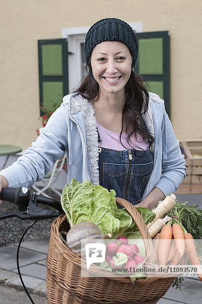 Portrait of a mid adult woman with bicycle and vegetables standing in front of wholefood shop