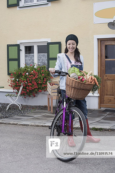 Portrait of a mid adult woman with bicycle and vegetables standing on street in front of wholefood shop