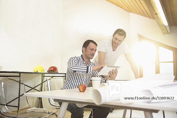 Architects discussing about project on digital tablet in office  Bavaria  Germany