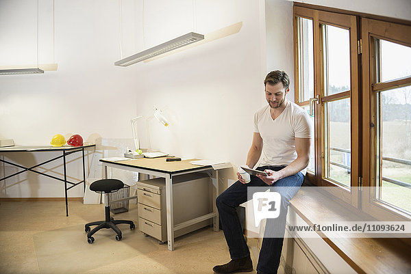 Architect sitting on window sill and working on digital tablet  Bavaria  Germany