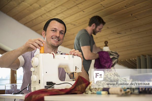 Male dressmaker stitching cloth on sewing machine with his colleague in background  Bavaria  Germany
