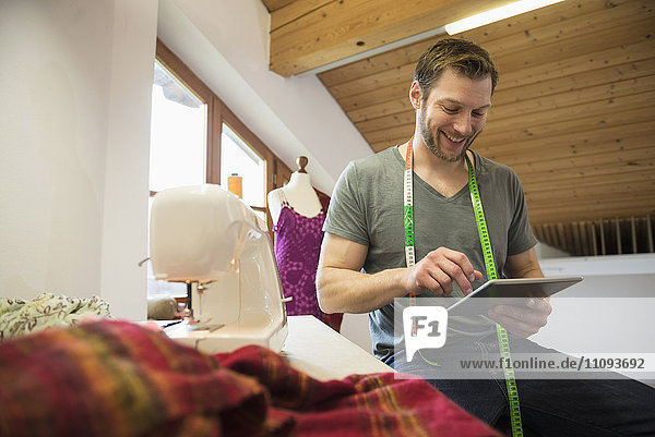 Male dressmaker working on digital tablet with sewing machine  Bavaria  Germany