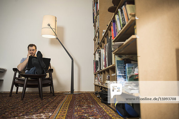 Mid adult man working on laptop in living room  Munich  Bavaria  Germany
