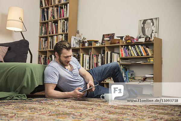 Mid adult man using digital tablet in living room  Munich  Bavaria  Germany
