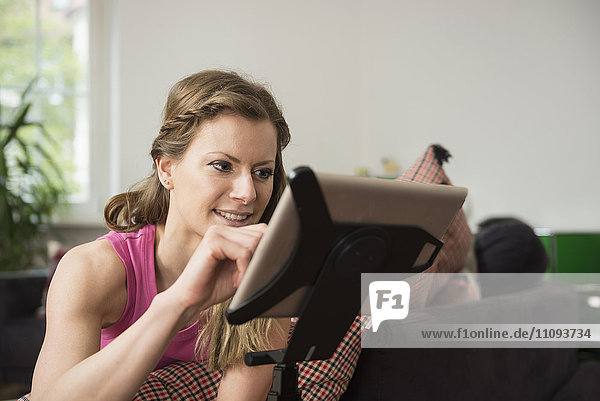 Young woman using digital tablet in living room and smiling  Munich  Bavaria  Germany