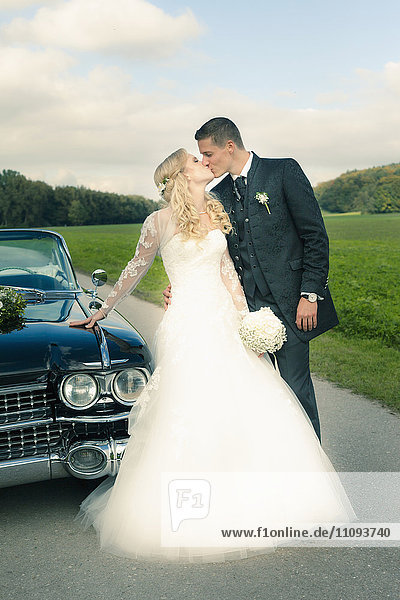 Newlywed couple kissing next to car