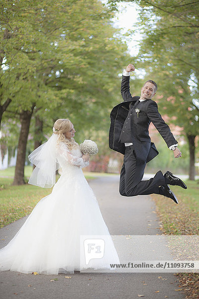 Bride holding bouquet and groom jumping in tree avenue
