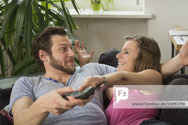Couple fighting for remote in living room  Munich  Bavaria  Germany